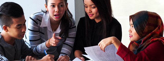 Motivate Students with a Team Approach to Learning. Enlist their peers, parents, and former teachers to find out what best motivates your students. | The image shows four high school students discussing a paper.