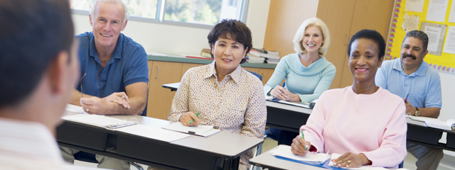 How to prepare for a strong parent-teacher conference. Parents sit in the classroom at desks.
