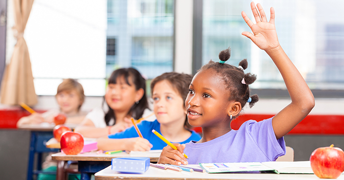 The Security of Classroom Routines | A row of children sitting in desks raise their hands.