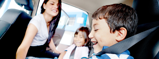 Parents Pulling Students from School Early? Share These 3 Tips with Them. | A mother puts a seatbelt on her son before they leave for the holidays.